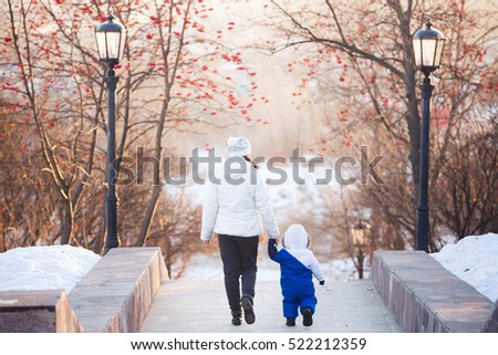 Young happy Mother with her baby son enjoying beautiful cold winter sunny day. Happy family lifestyle concept with sunshine and blue sky, back silhouette view