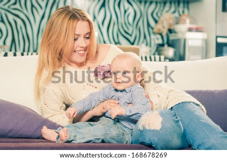 young happy mother with her son on a sofa - stock photo