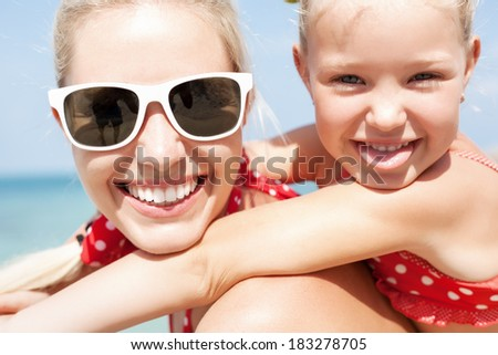 Young happy mother with little girl on her back. Closeup of Happy family having fun at beach in summer - stock photo