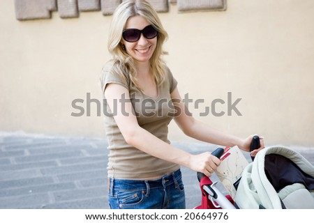 Young happy mother with stroller on street - stock photo