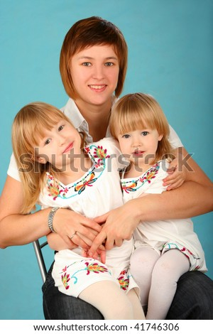 Young happy mother with two small daughters on blue  background