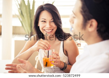 Young happy multi ethnic couple in love have an aperitif in a city scape during a sunny day