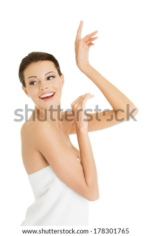Young happy naked woman covering her self with towel on white background.