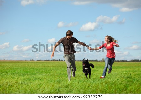 Young happy pair running on green meadow with a dog - stock photo