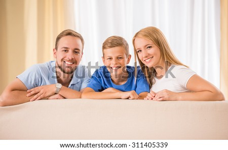 Young happy parents and their teenage son are posing at home, smiling. - stock photo