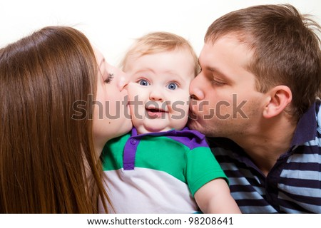 Young happy parents kissing baby boy