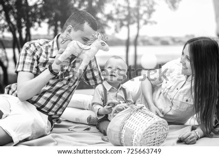 Young happy parents playing with little son outdoor in the park, black and white