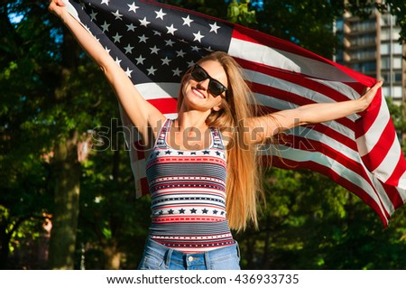 Young happy patriot girl holding the american, united states flag - stock photo