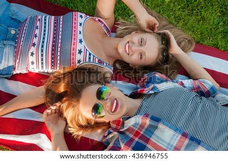 Young happy patriot women celebrating independence day  4th of july on the united states flag - stock photo