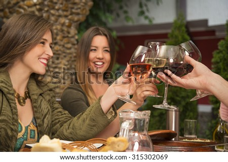 Young happy people celebrating during a lunch at a restaurant. They are smiling and toasting with wine. - stock photo