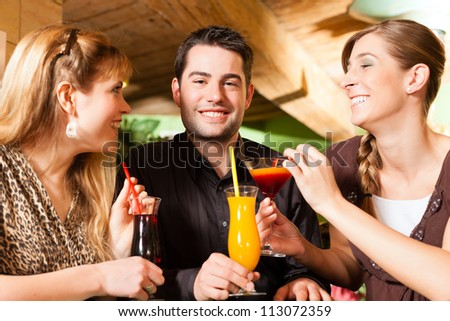 Young happy people drinking cocktails in bar or restaurant; presumably it is a little party - stock photo