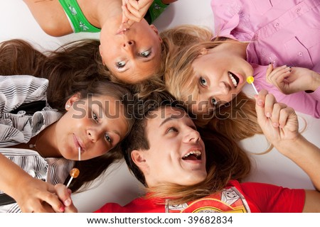 Young happy people lay with sugar candies on a white background.