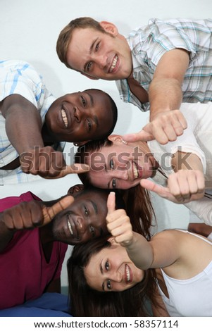 young, happy people of different backgrounds have fun and show their thumb in the direction of camera - stock photo