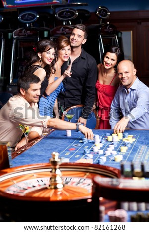 young, happy people playing the casino roulette - stock photo