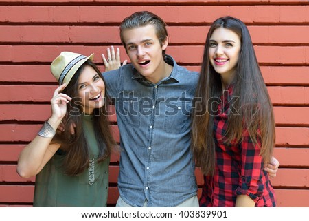 Young happy people posing against red brick wall. Urban lifestyle, happiness, joy, friends, teenage, first love concept. Image toned and noise added. - stock photo