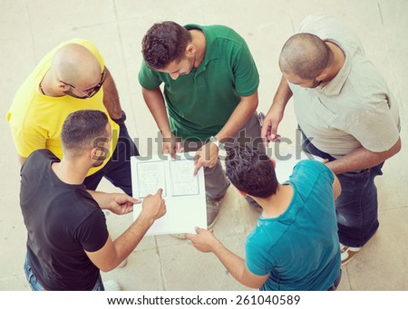 Young happy people standing and talking together on university campus - stock photo