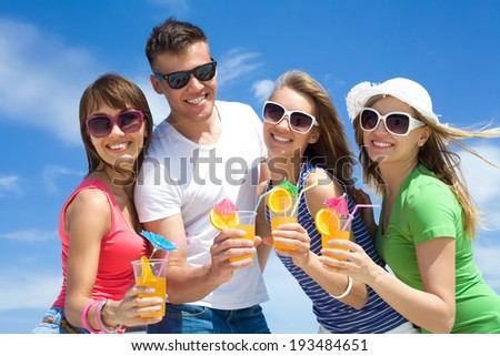 young happy people with cocktails in hand on outdoors - stock photo