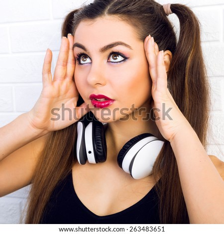 Young happy playful teen girl with two ponytails having fun and smiling, listening her favorite music on big white earphones, wearing stylish black outfit and bright make up, urban wall background. - stock photo