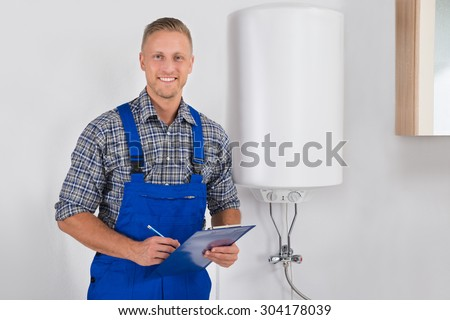 Young Happy Plumber In Overall Holding Clipboard And Pen - stock photo