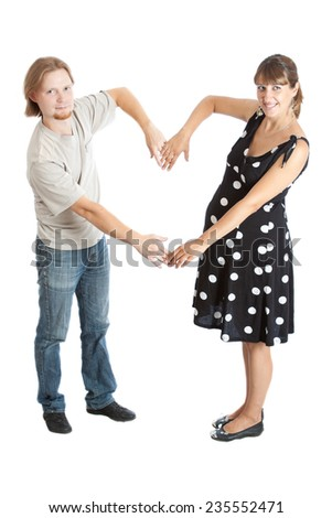 young happy pregnant woman and her husband take a heart sign - stock photo