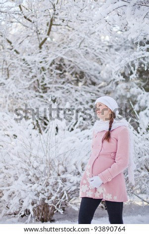 Young happy pregnant woman in snowy forest - stock photo