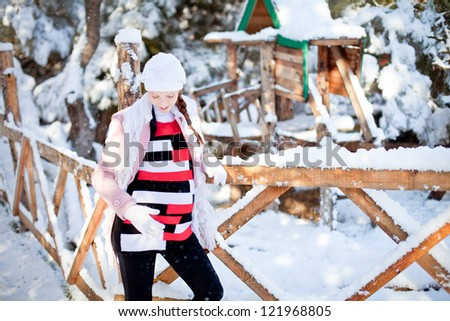 Young happy pregnant woman in snowy park - stock photo