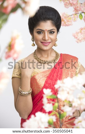 Young happy pretty Indian woman in traditional saree in flower garden in studio shoot. - stock photo