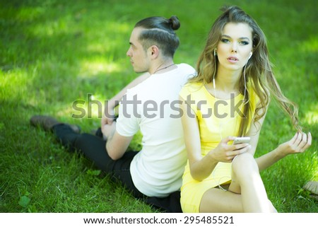 Young happy pretty pair relaxing in park sitting on green grass listening music on natural background, horizontal picture - stock photo