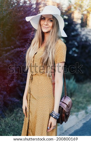 Young happy pretty woman posing in city garden in stylish retro hat and outfit, smiling and having fun alone. Retro style. - stock photo