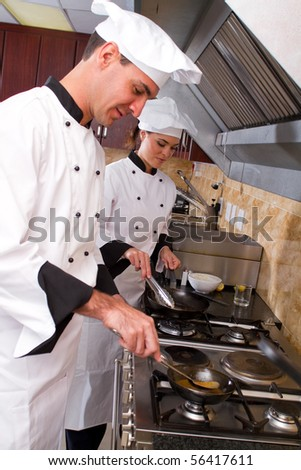 young happy professional chefs in kitchen