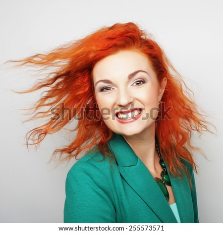 Young happy red woman with wind in hair - stock photo