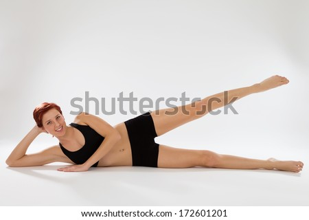 young happy redhead fitness woman exercising with her legs