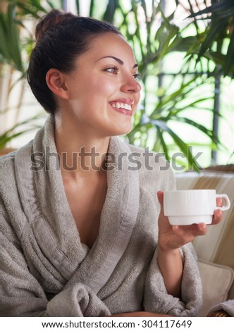 Young happy relaxed woman drinking tea at spa resort