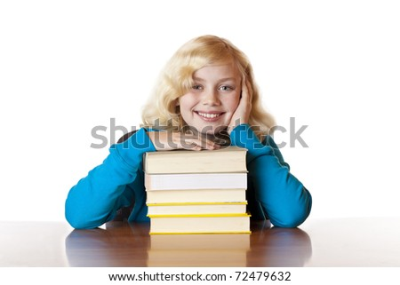 Young happy school girl sitting with books at desk. Isolated on white background. - stock photo