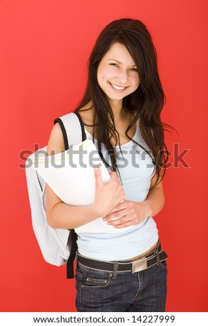 Young happy schoolgirl with backpack, holding notebook. Looking at camera. Front view. - stock photo