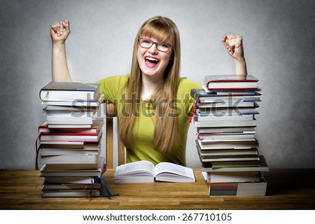 young happy schoolgirl with glasses and lots of books at a table - stock photo