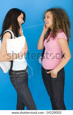 Young happy schoolgirls with backpack, holding notebook and listening to music by headset. Side view. - stock photo