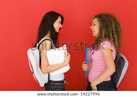 Young happy schoolgirls with backpack, holding notebook. Side view. - stock photo