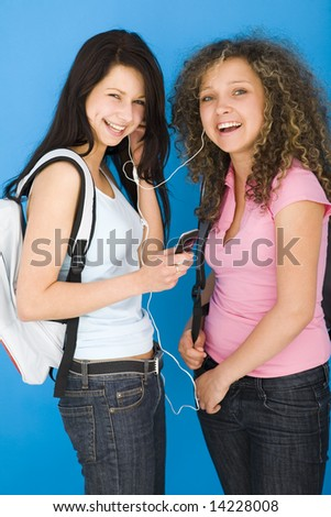 Young happy schoolgirls with backpack listening to music by headset. one of they holding mobile phone. Looking at camera. Side view. - stock photo