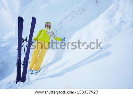 Young happy skier woman standing with ski leaning on huge snowdrift. With lot's of copy space - stock photo