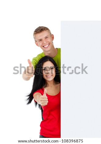 young happy smile couple standing hold pointing thumb up finger gesture at blank board, handsome guy attractive girl wear green red shirt, isolated over white background, studio shoot - stock photo
