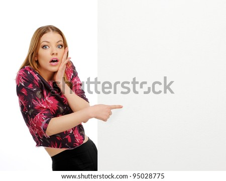 young happy smile woman peeking over edge of blank empty paper billboard with copy space for text, isolated over white background - stock photo
