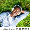 Young happy smiling african american lying on a grass and listens to music in a park - stock
