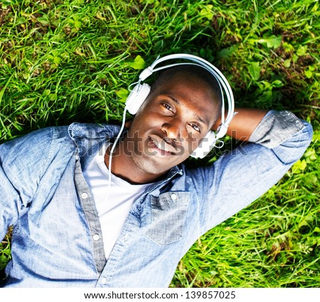 Young happy smiling african american lying on a grass and listens to music in a park - stock photo