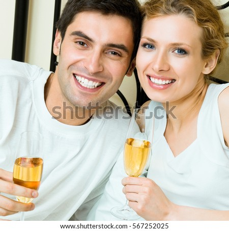 Young happy smiling amorous couple celebrating with champagne at bedroom