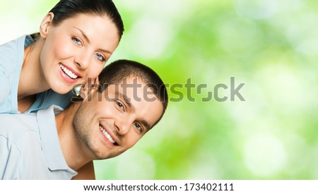 Young happy smiling attractive couple, outdoors. To provide maximum quality, I have made this image, by combination of three photos. You can use left part for slogan, big text or banner. - stock photo