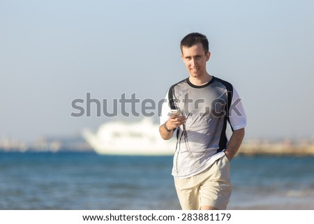 Young happy smiling attractive man holding cellphone, using app, making call, messaging text or dialing number, walking at seashore from white yacht - stock photo