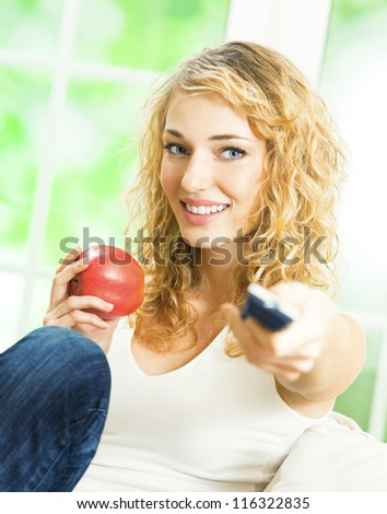 Young happy smiling blond woman watching TV at home - stock photo