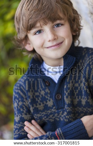 Young happy smiling boy outside arms folded - stock photo