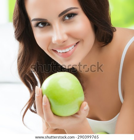 Young happy smiling brunette woman with green apples, indoors. Healthy eating, beauty and dieting concept. - stock photo
